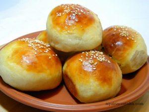pãozinho recheado em cima de um prato de barro