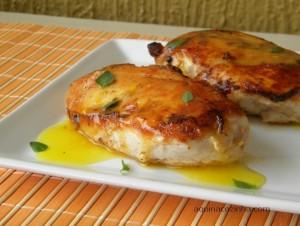 Filé de frango com molho de laranja em cima de um prato branco com ervas em cima